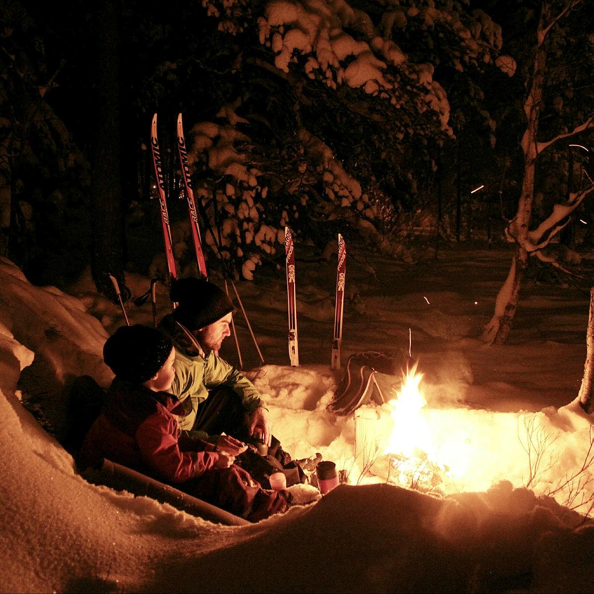 Nyt romjulskvelden foran bålet i skogen.