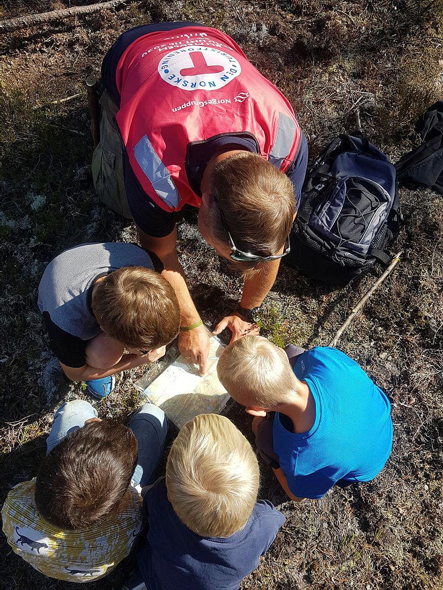 Tore ser på kart med barna og viser dem hvordan de kan finne ut hvor de er.