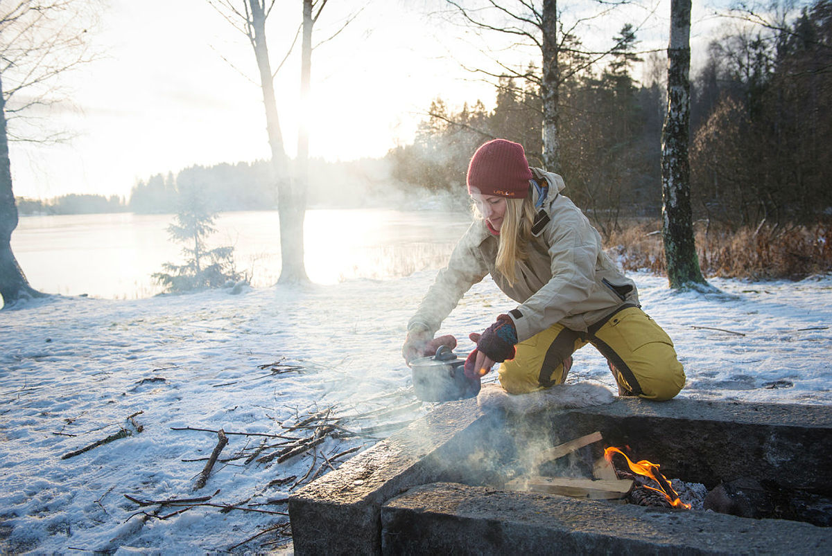 Maria Almli fra Norges Jeger- og Fiskeforbund lager einerøkt ørret på bål.