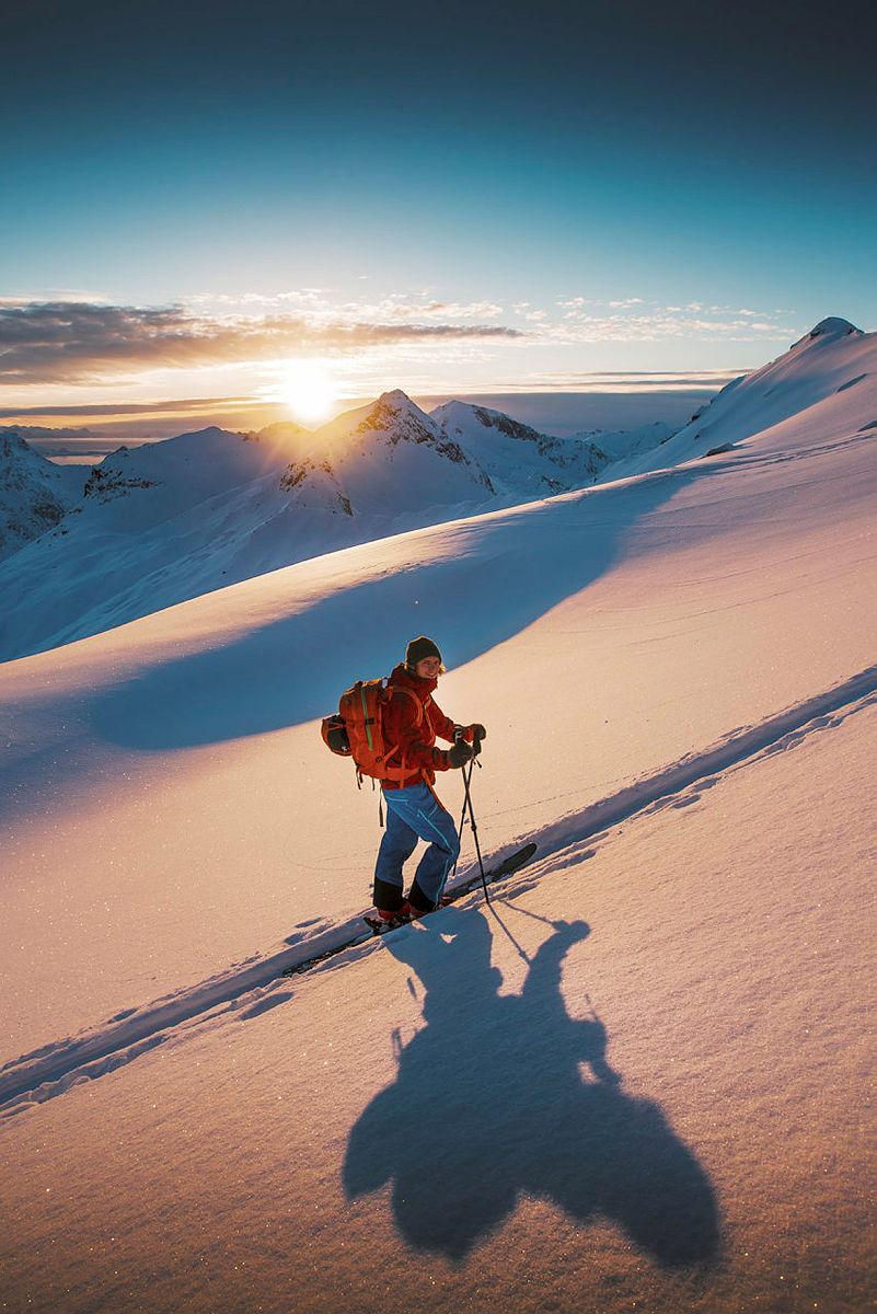 Januar-sola har nettopp begynt vise seg i toppene. Hermann Glasius Hegg koser seg med et ferdig trÂkket spor opp mot Torskmannen(Lofoten) pen av Ârets beste pudderdager!