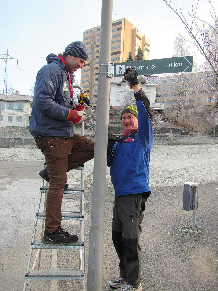 Medhi Maghsoudi og Odd Fjeldstad, frivillige i DNT Oslo og Omegn, monterer skilt ved Trosterud T-banestasjon.