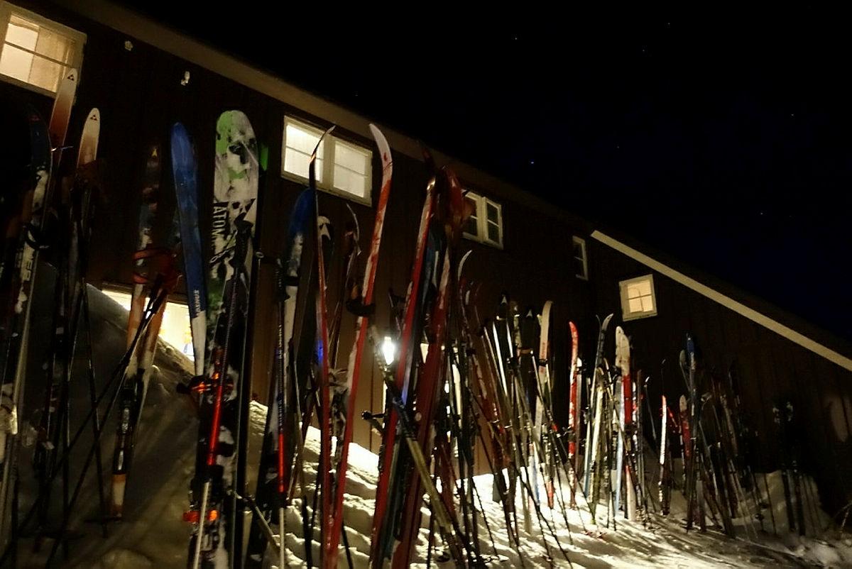 Ski i snøen ved hytteveggen