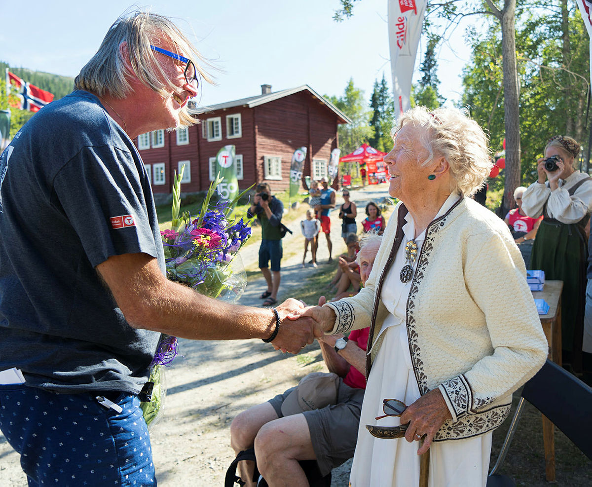 Tinn-ordfører Bjørn Sverre Birkeland overrekker blomster til Ragnhild Helberg, som i over 50 år var gift med Claus Helberg.