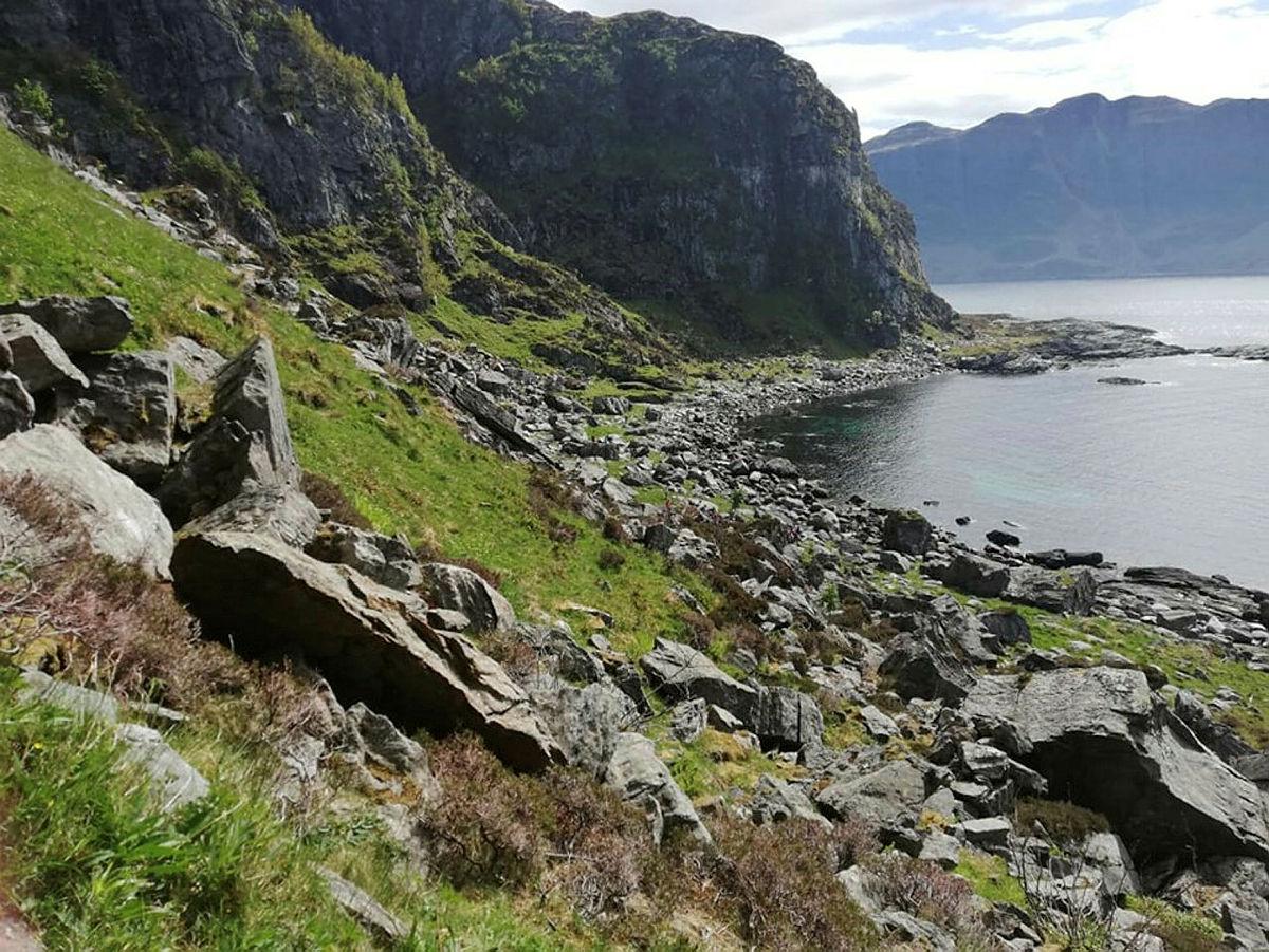 Stien går langs fjæresteinene, gjennom ura og over neset.