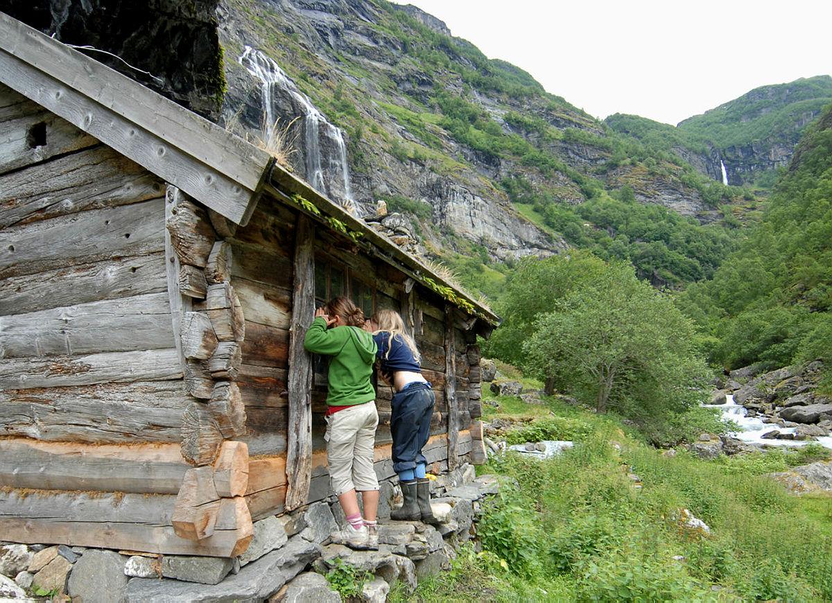 Nysgjerrige barn titter inn gjennom vinduet på husmannsplassen Almen i Aurlandsdalen.