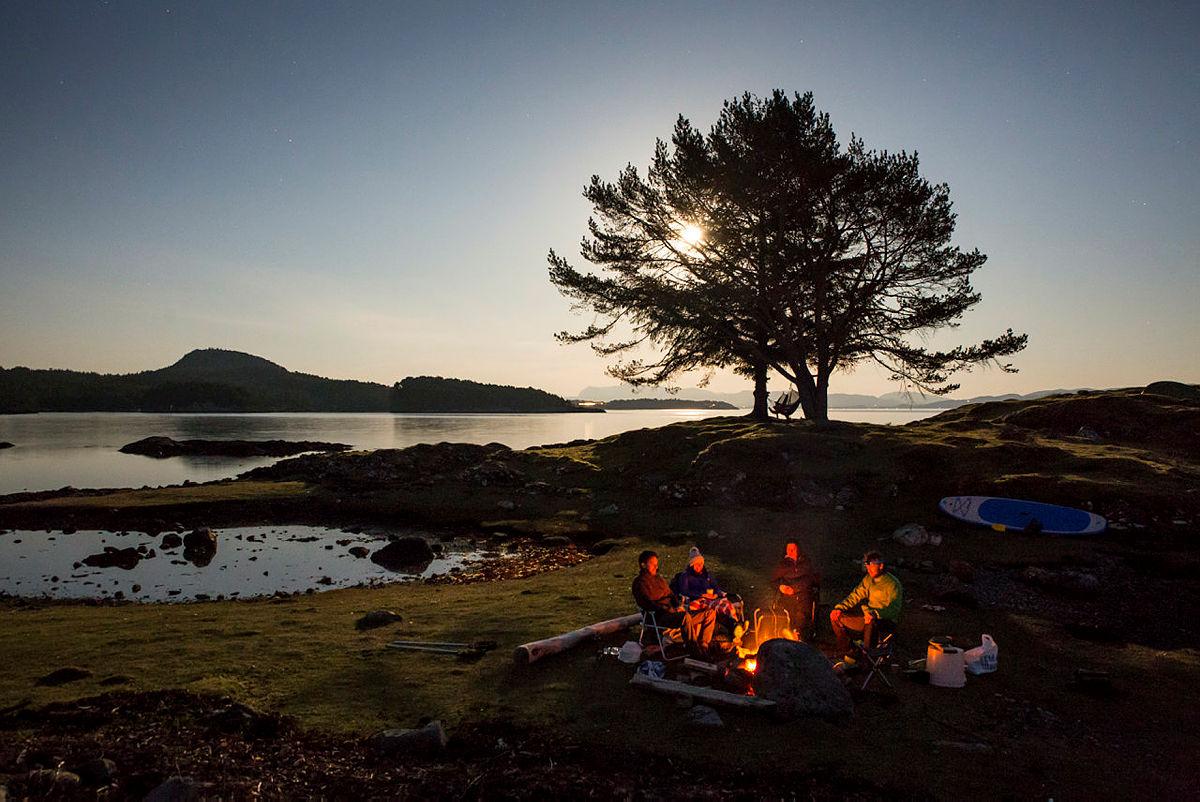 Å sitte sammen med gode venner rundt et sent sommerbål er herlig. Telttur på Kuskjæret ved Bjørnafjorden i Os kommune.