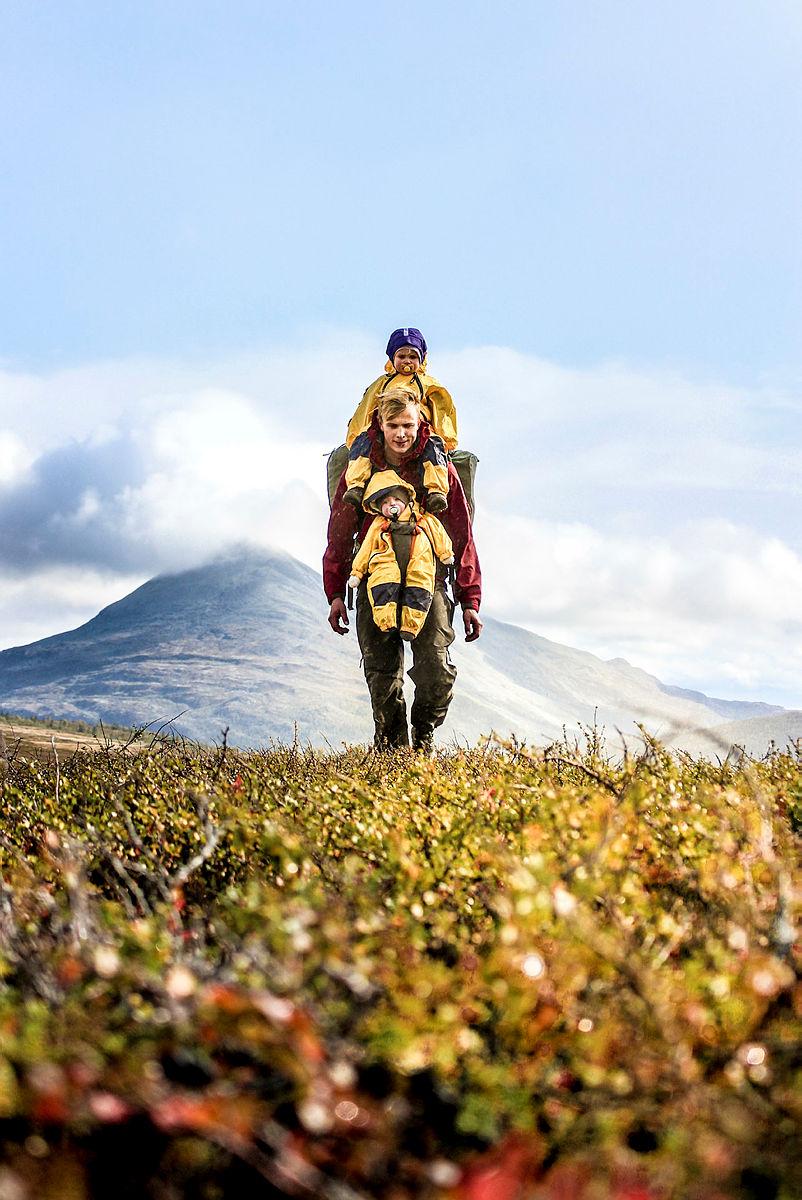 Hardangervidda, like nord for Rjukan med Gaustatoppen i bakgrunnen. Far, datter og sønn på telttur med hjemmesydd bæresele og dunposer.