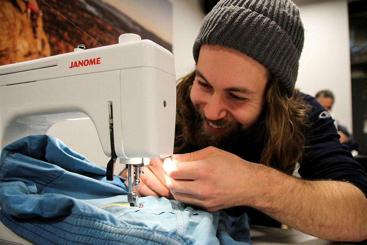 Ødelagt utstyr blir som nytt når Isak Bjørn reparerer en jakke på Fiksefest på Friluftshuset.
