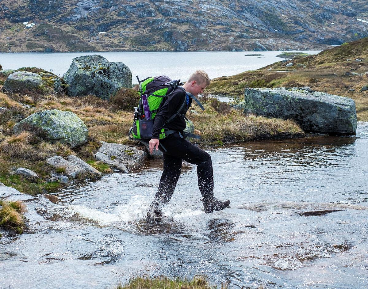 FUKTIG: Svein Kjetil Egeland forsøker å komme seg over bekken uten å bli våt på føttene.