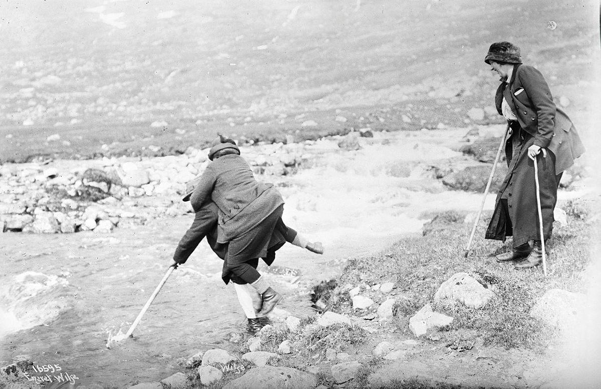 En kvinne bæres over en elv i 1914